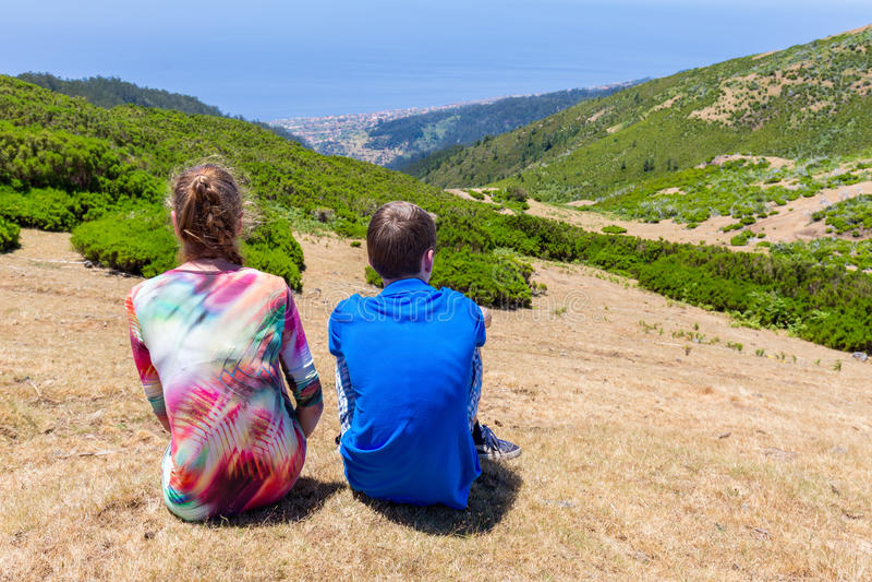 La madre caucásica y el hijo que se sientan en montaña ajardinan imagen de archivo libre de regalías