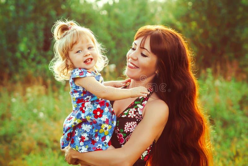La madre celebra al bebé en sus brazos imagen de archivo