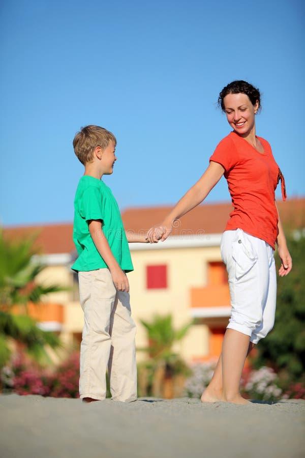 La madre celebra al muchacho en la mano en la playa fotos de archivo libres de regalías