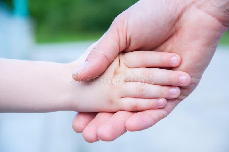 La madre celebra la mano de un pequeño niño De com?n acuerdo foto de archivo libre de regalías