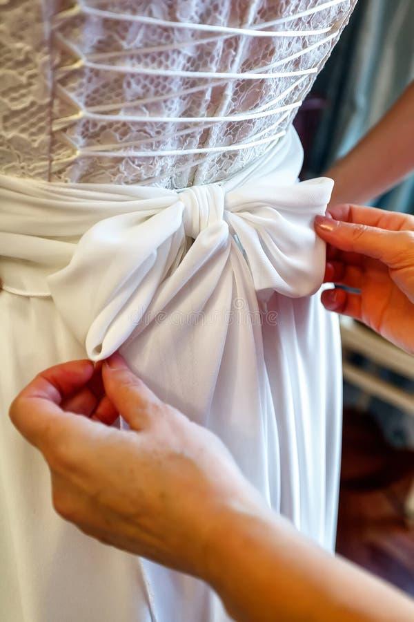 La madre che aiuta sua figlia si veste per nozze fotografia stock