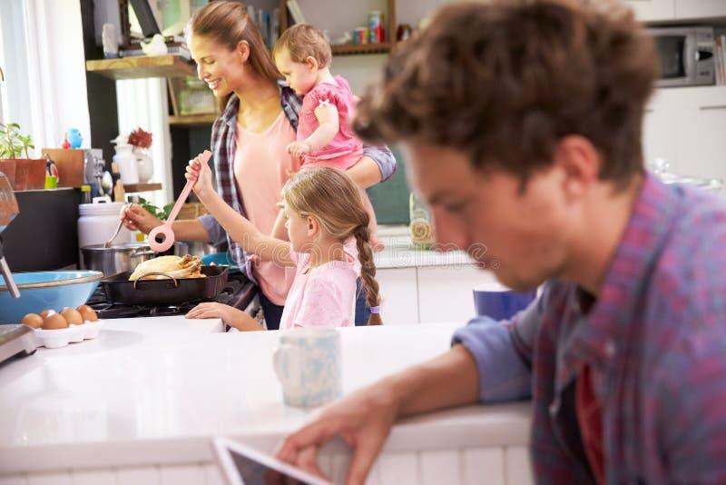 La madre cocina la comida de la familia mientras que padre Uses Digital Tablet fotografía de archivo libre de regalías