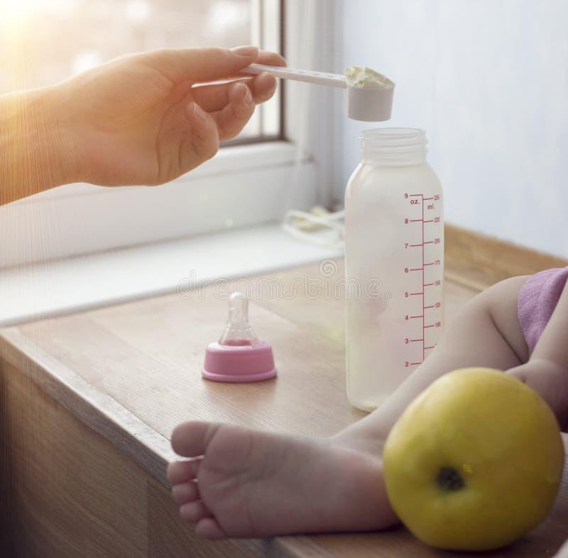 La madre cocina los alimentos para niños para el niño, un cierre para arriba, una mano y una pequeña botella foto de archivo