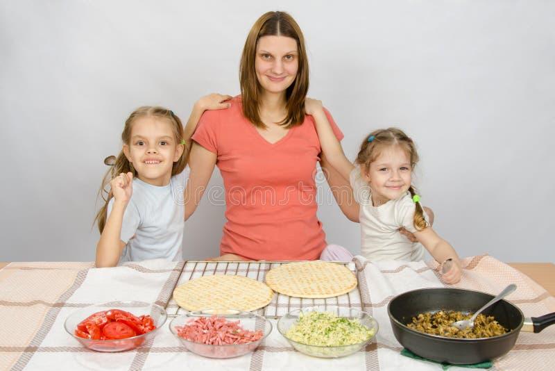 La madre con dos hijas en la tabla de cocina va a cocinar una pizza y una mirada de la diversión en el marco foto de archivo libre de regalías