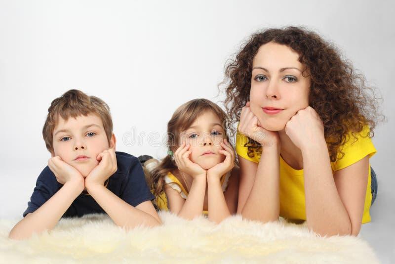 La madre con dos niños serios miente encendido se cayó foto de archivo