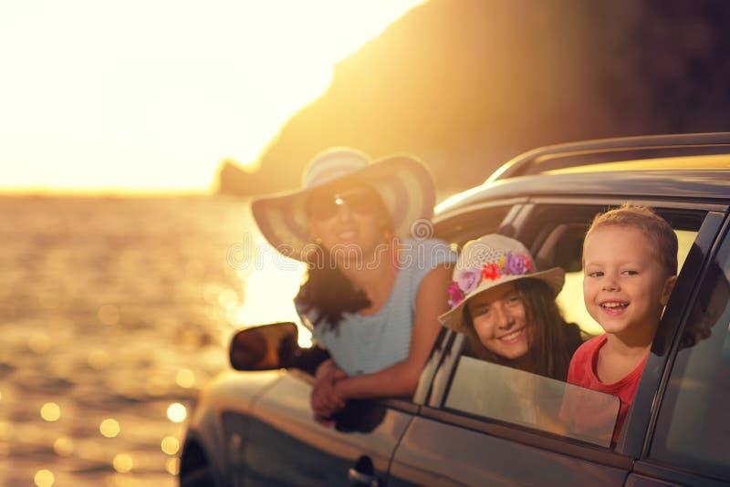 La madre con dos niños viaja en coche el las vacaciones de verano, puesta del sol imagenes de archivo