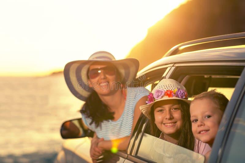La madre con dos niños viaja en coche en puesta del sol de las vacaciones de verano imagenes de archivo