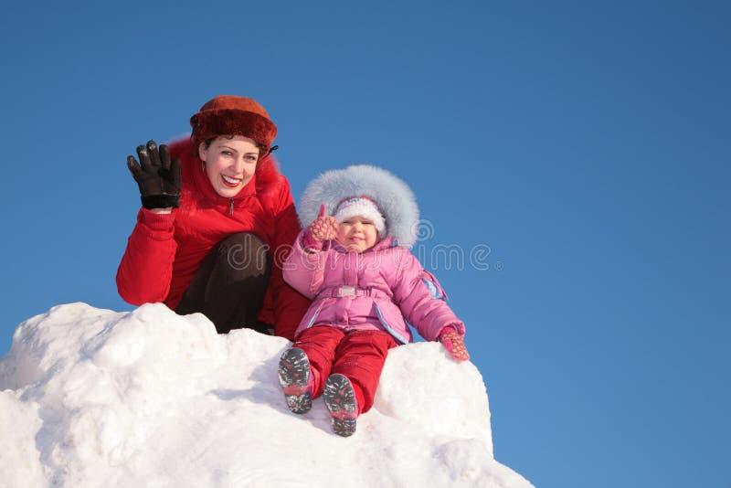 La madre con el niño se sienta en la colina de la nieve fotos de archivo libres de regalías