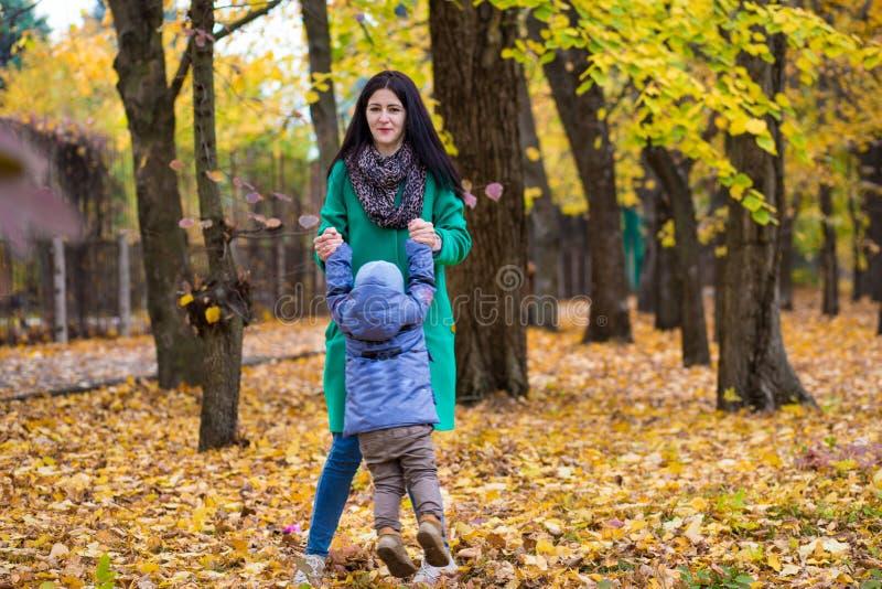 La madre con el pequeño hijo juega en parque del otoño fotografía de archivo