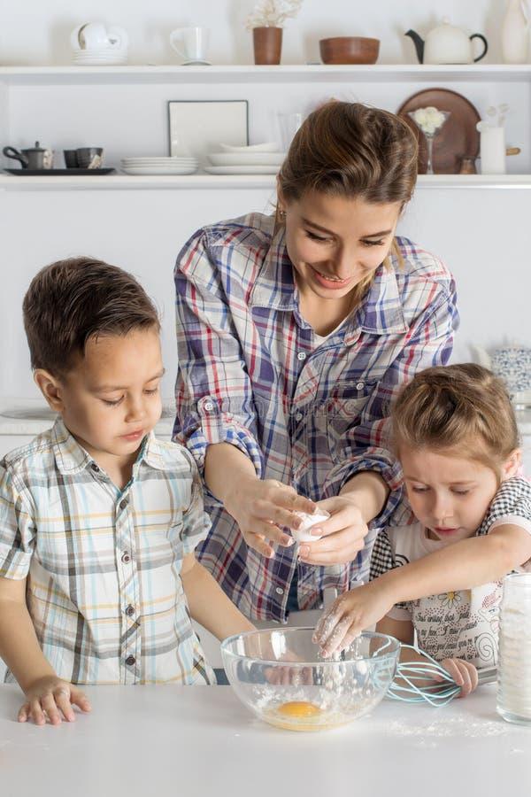 La madre con la hija y el hijo hacen junta la pasta en kitche fotografía de archivo