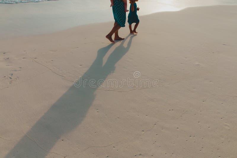 La madre con i bambini cammina sulla spiaggia del tramonto immagini stock