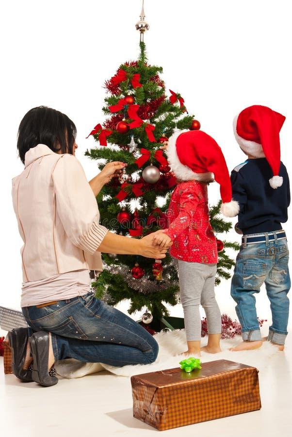 La madre con i bambini decora l'albero immagine stock libera da diritti
