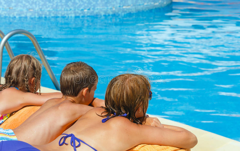 La madre con i suoi bambini si avvicina alla piscina. immagine stock