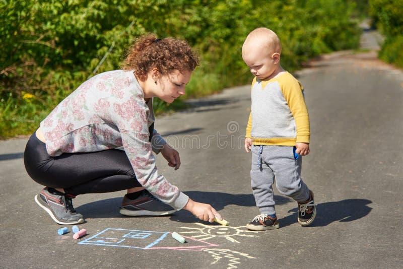 La madre con il suo piccolo figlio disegna un gesso variopinto su asfalto un giorno di estate Attivit? del bambino e della mamma fotografia stock libera da diritti