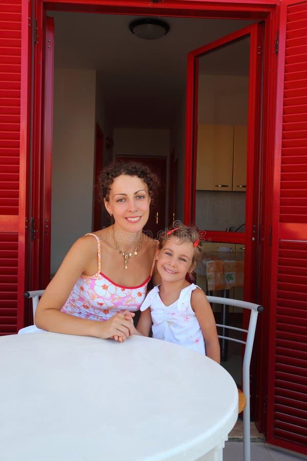 La madre con la figlia si siede sulla veranda fotografia stock libera da diritti
