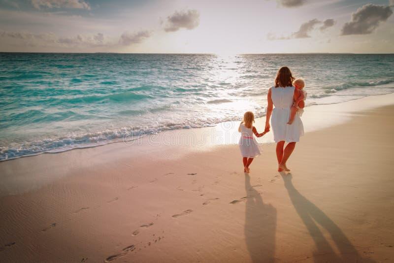 La madre con los niños camina en la playa de la arena fotos de archivo