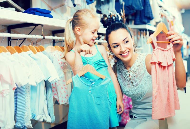 La madre con los niños de compra de la hija viste en tienda imágenes de archivo libres de regalías