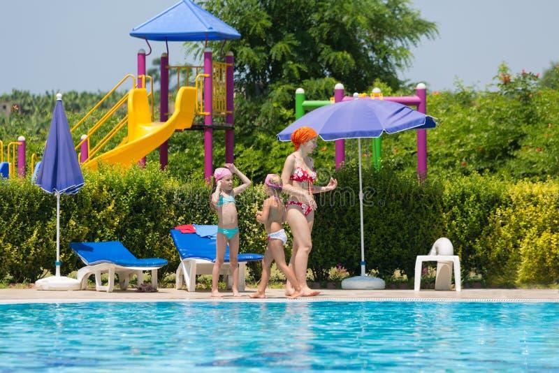 La madre con los niños pasa tiempo alrededor de la piscina imagenes de archivo