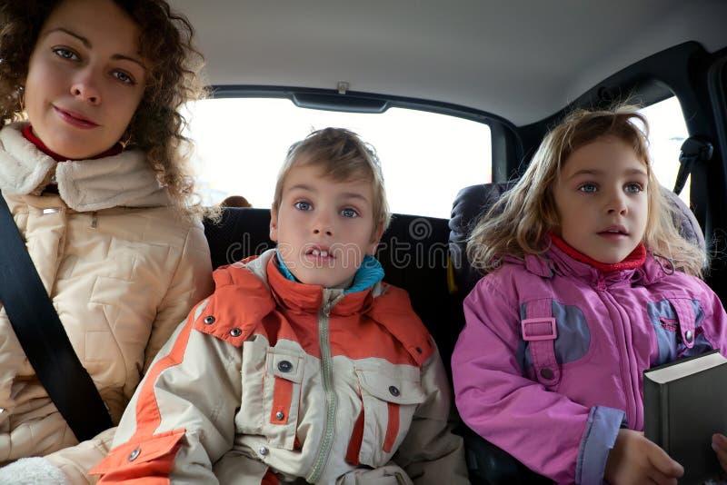 La madre con los niños se sienta en el asiento trasero del coche fotos de archivo