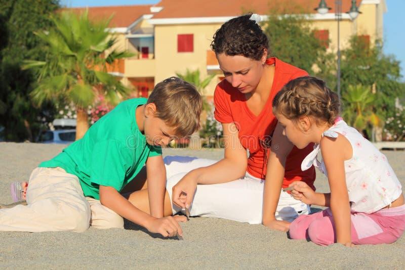La madre con los niños se sienta en la playa y el drenaje imagen de archivo libre de regalías