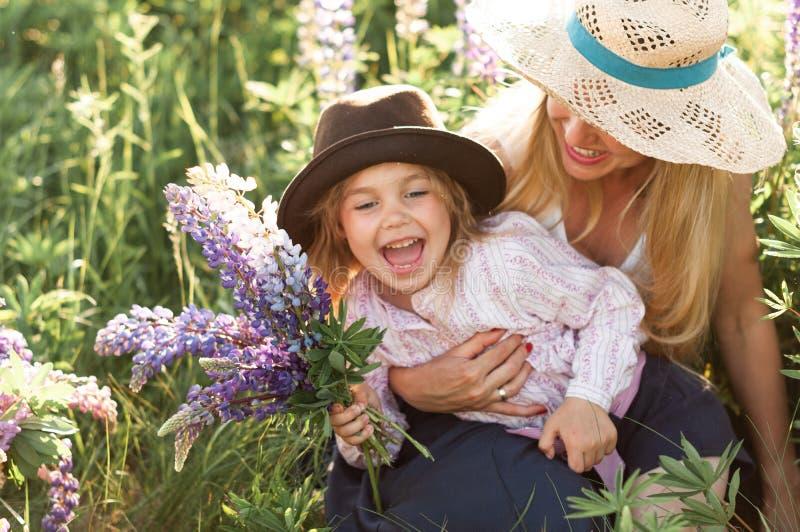 La madre con la pequeña hija se divierte en el campo foto de archivo libre de regalías