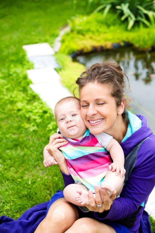 La madre con su bebé se divierte cerca del lago fotos de archivo