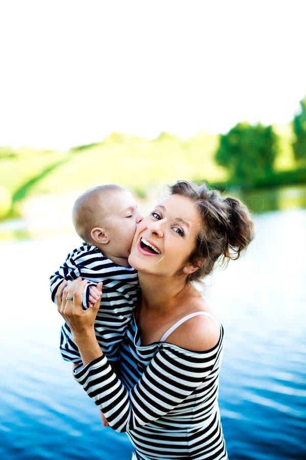 La madre con su bebé se divierte cerca del lago foto de archivo libre de regalías