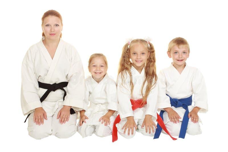 La madre con su hija y un muchacho con su hermana que se sienta en un karate plantean ritual imagen de archivo