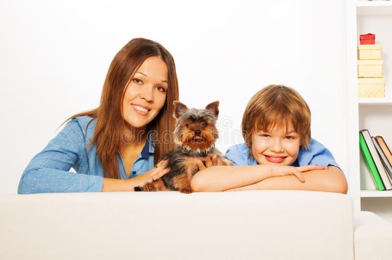 La madre con su hijo y el perro de Yorkshire ponen en el sofá fotos de archivo