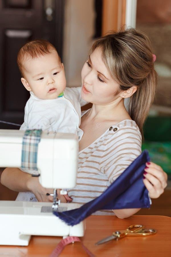 La madre con un bebé muestra su trabajo, cosiendo en casa Criar a niños, cuidado de niños, niñera foto de archivo
