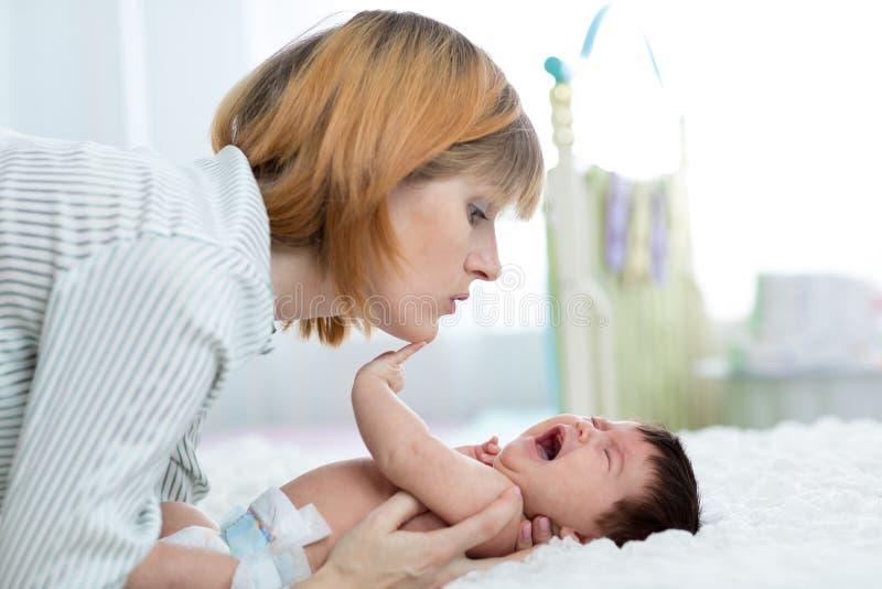La madre conforta a su bebé recién nacido gritador fotografía de archivo