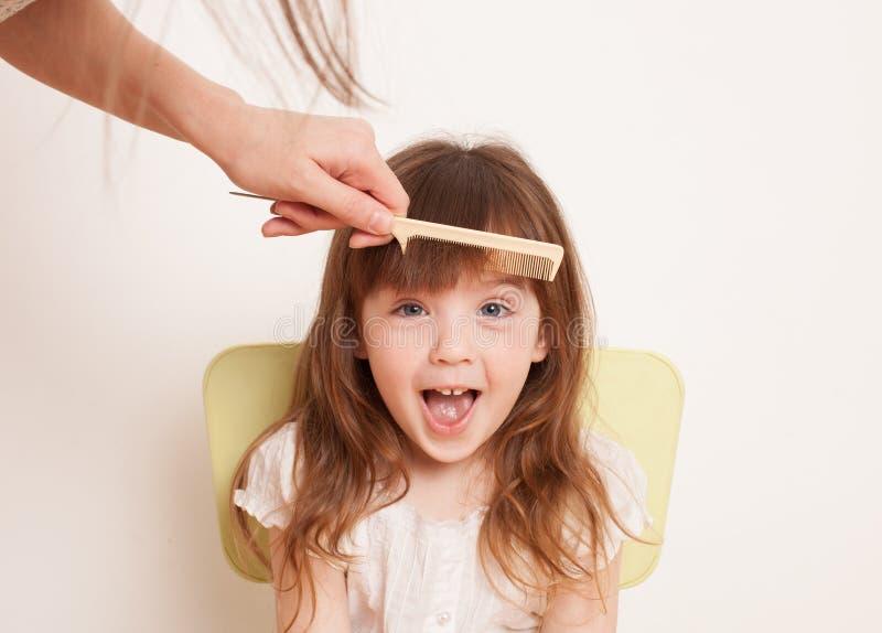 La madre corta el pelo del ` s de la hija en casa imagenes de archivo