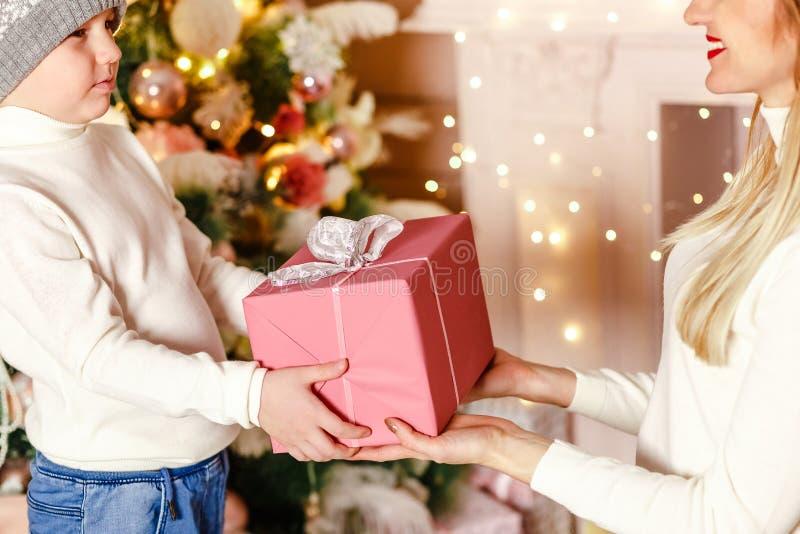 La madre dà un regalo a suo figlio per il Natale Bello contenitore di regalo a disposizione vicino fotografie stock libere da diritti