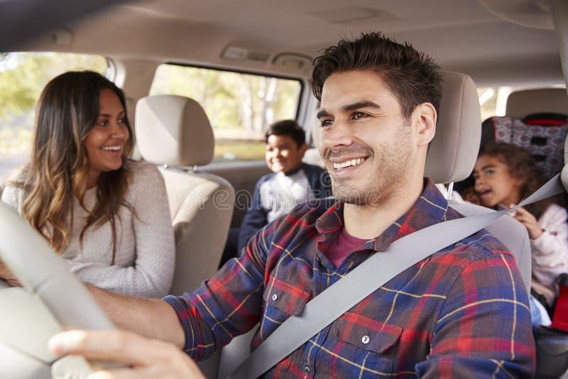 La madre da vuelta alrededor a sus niños en el asiento trasero del coche imagenes de archivo