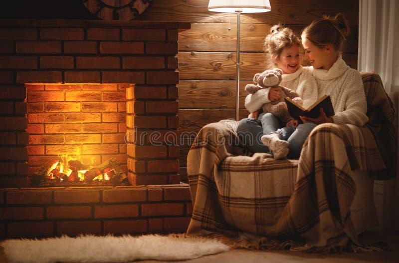 La madre de la familia y la hija felices del niño leyeron el libro en eveni del invierno imagen de archivo libre de regalías