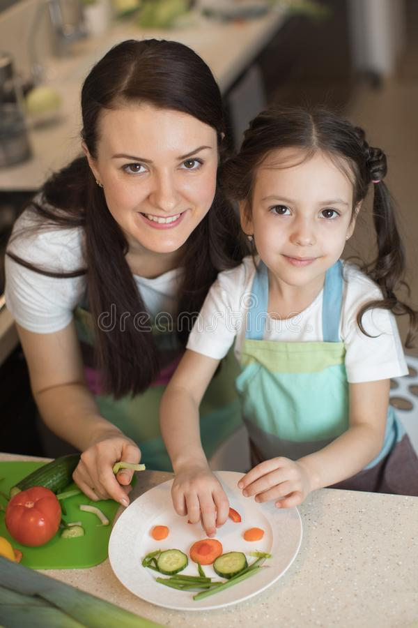 La madre de la familia y la muchacha felices del niño están preparando la comida sana, ellos improvisan juntas en la cocina fotografía de archivo libre de regalías