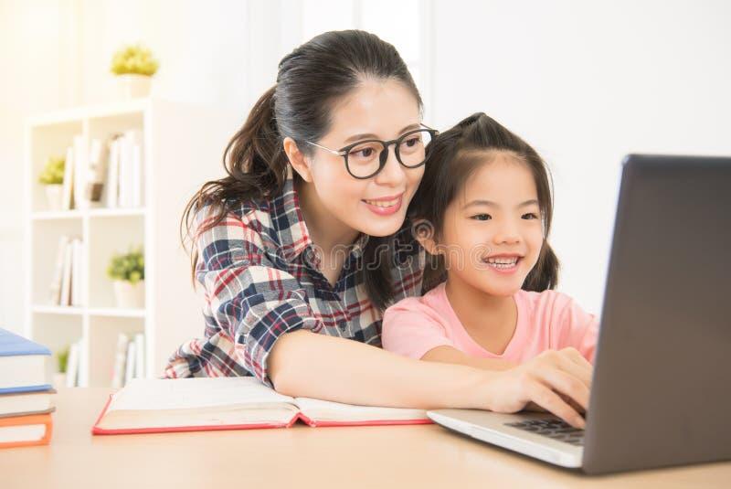 La madre de la sonrisa dejó a sus niños saber usando el ordenador portátil fotos de archivo libres de regalías