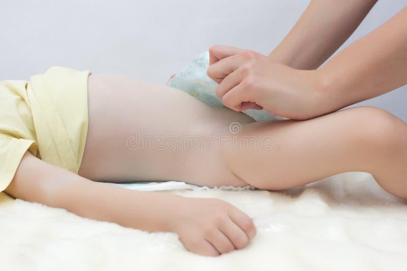 La madre de la muchacha pone un pañal a una muchacha caucásica del pequeño bebé, vistiendo un panal a su hija, blanca imagen de archivo libre de regalías