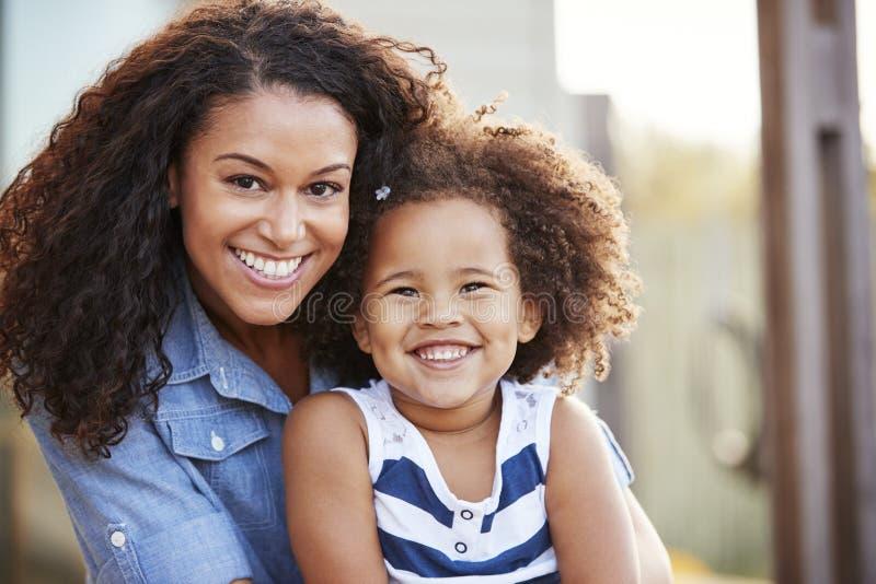 La madre de la raza mixta y la hija joven sonríen a la cámara afuera imagenes de archivo