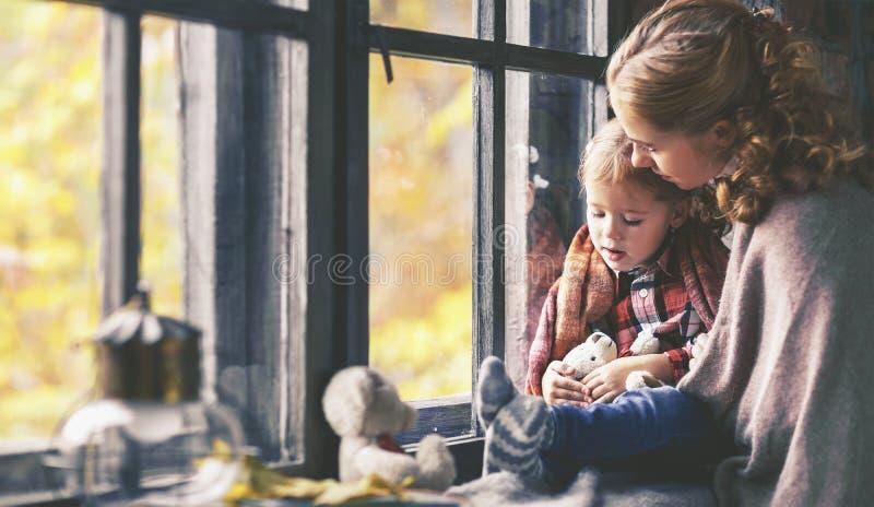 La madre della famiglia e la figlia del bambino guardano fuori la finestra sull'autunno piovoso immagini stock libere da diritti
