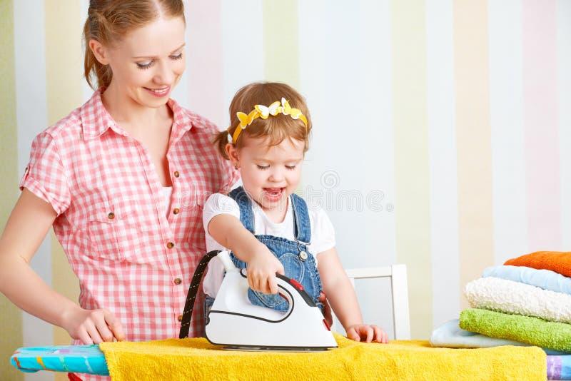 La madre della famiglia e la figlia del bambino si sono impegnate insieme in lavoro domestico ir fotografia stock libera da diritti