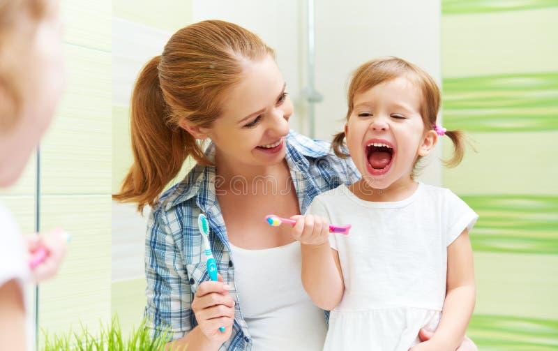 La madre della famiglia e la ragazza felici del bambino pulisce i denti con lo spazzolino da denti immagine stock libera da diritti
