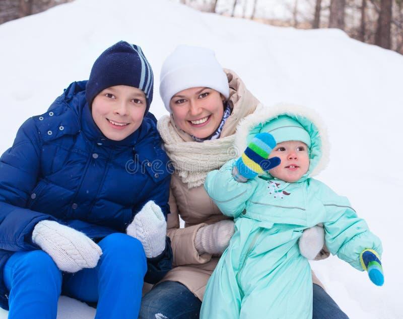 La madre della famiglia ed il bambino e l'adolescente felici nell'inverno parcheggiano fotografie stock