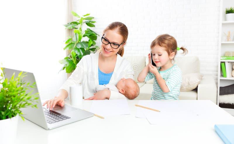 La madre di affari lavora a casa via Internet con il loro bambino immagine stock
