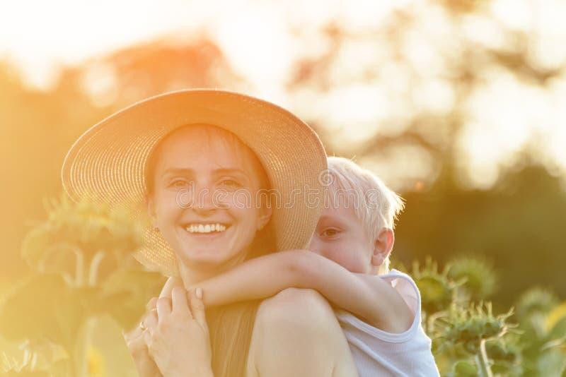 La madre di risata felice che dà il giro di a due vie del figlio del bambino su fondo dei girasoli soleggiati di fioritura verdi  immagine stock