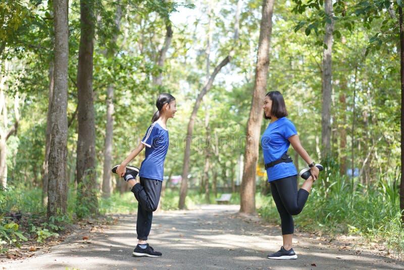 La madre e la figlia asiatiche si scaldano prima di correre al parco immagini stock libere da diritti