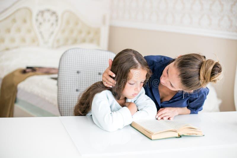 La madre e la figlia felici della famiglia hanno letto un libro nell'uguagliare a casa  immagini stock
