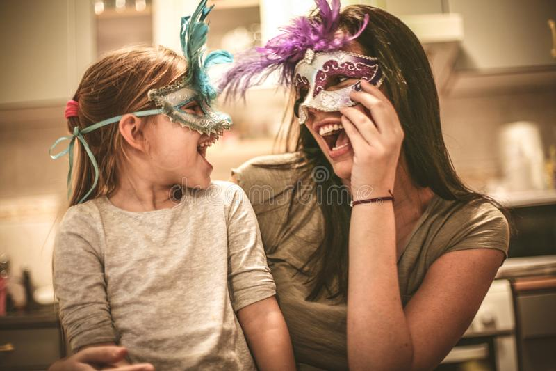 La madre e la figlia hanno gioco con la maschera di carnevale immagine stock libera da diritti