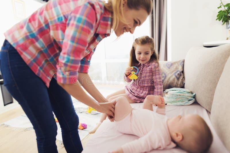 La madre e la figlia prendono la cura del bambino all'interno fotografia stock