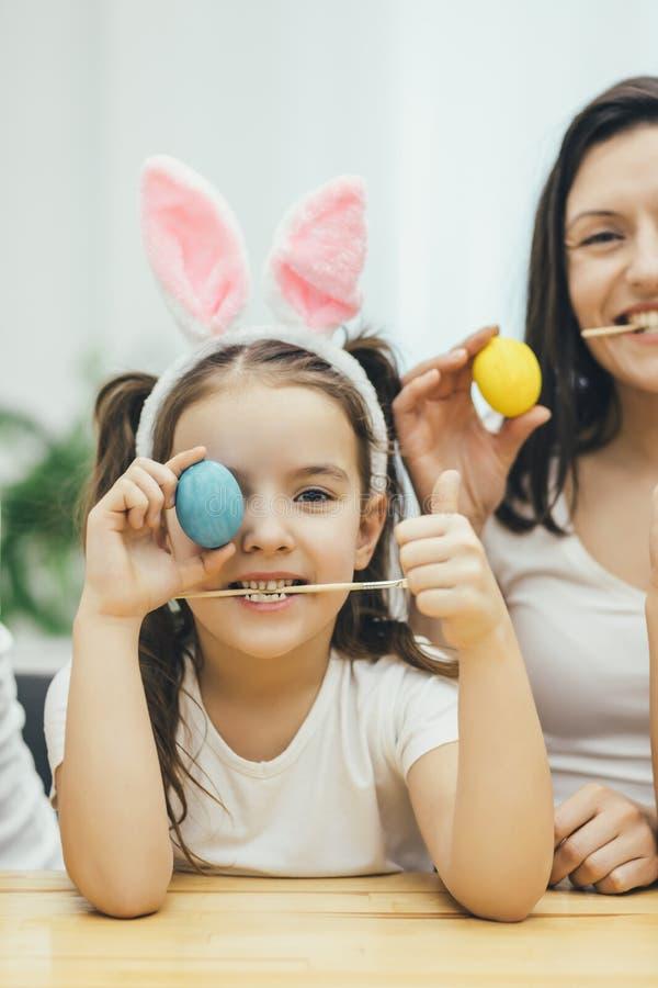 La madre e la figlia sono pronte per Pasqua Piccolo ragazza sveglia che nasconde il suo occhio dietro l'uovo blu, pennello in suo fotografia stock
